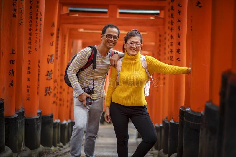 Kyoto Japón - november9,2018: el turista asiático de los pares que toma una foto en el polo de madera rojo del inari del fushimi  fotos de archivo