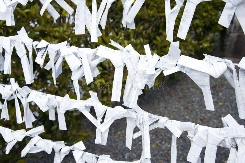 Kyoto Japan —berlock av pappers- förmögenhet på en linje i en tempel Omikuji förutsägelser arkivfoton