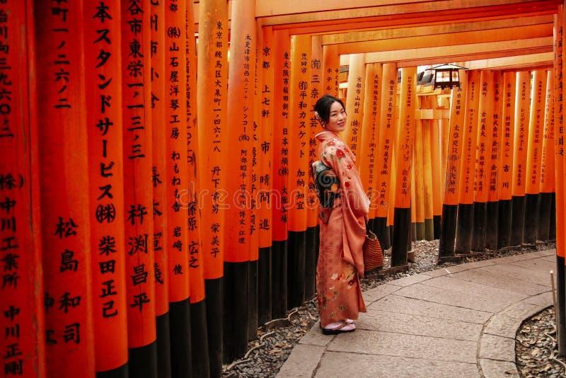 KYOTO JAPAN - APRIL 02, 2019: Flicka i traditionell japansk kimono i röda Torii portar i den Fushimi Inari relikskrin i Kyoto, J royaltyfri foto