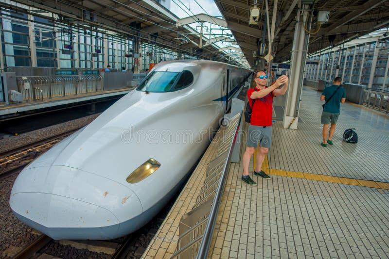 KYOTO, JAPAN - JULI 05, 2017: De niet geïdentificeerde mens die een selfie met een erachter trein tajing, JR700 shinkansen ultras stock foto's