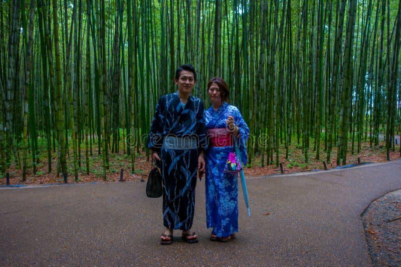 KYOTO, JAPAN - JULI 05, 2017: Het niet geïdentificeerde paar stellen bij camera in een weg bij mooi bamboebos in Arashiyama royalty-vrije stock afbeeldingen