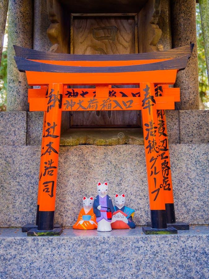 KYOTO JAPAN - JULI 05, 2017: Tre katter av porslin på den röda Tori Gate på Fushimi Inari förvarar i Kyoto, Japan fotografering för bildbyråer