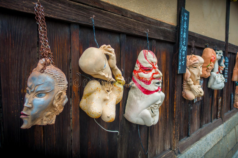 KYOTO, JAPAN - JULY 05, 2017: Halloween masks hanging ina wooden wall in outdoors, located in the center of Gion street. Of Kyoto, Japan stock photo