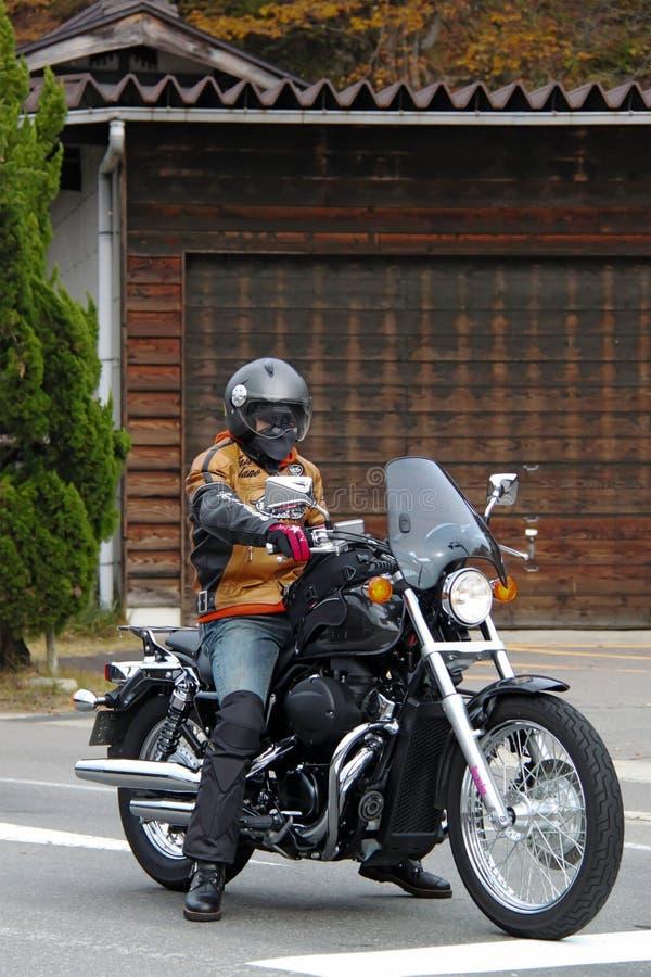 Man on motorcycle ready to depart. Gifu Prefecture, Japan - 2010: Man on motorcycle ready to depart at Shirakawago Village stock images