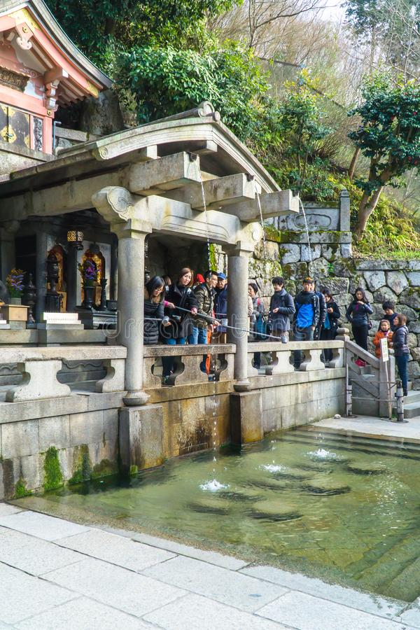 Kyoto, Japan - MAR 2, 2015: Otowa Waterfall inside Kiyomizu-dera. The waterfall are divided into three streams and visitors use c. Ups attached to long poles to royalty free stock photos