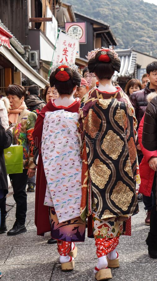 Kyoto, Japan - March 2015: Beautiful Japanese Geisha with beautiful kimono walking along the street in Kyoto Japan. Kyoto, Japan -March 2015: Beautiful Japanese royalty free stock photos