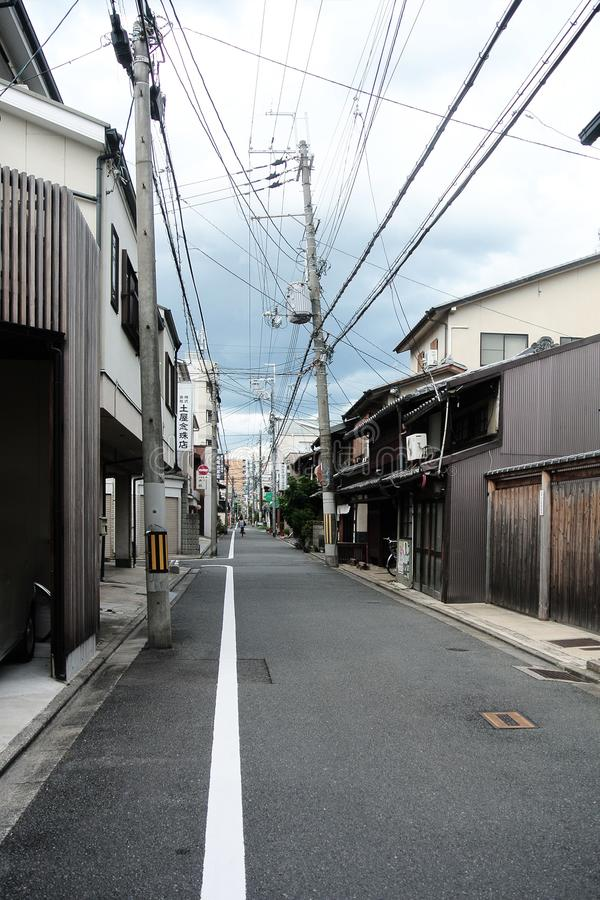 Narrow rural street in city of Kyoto with old traditional japanese buildings made of wood and crooked power poles royalty free stock images