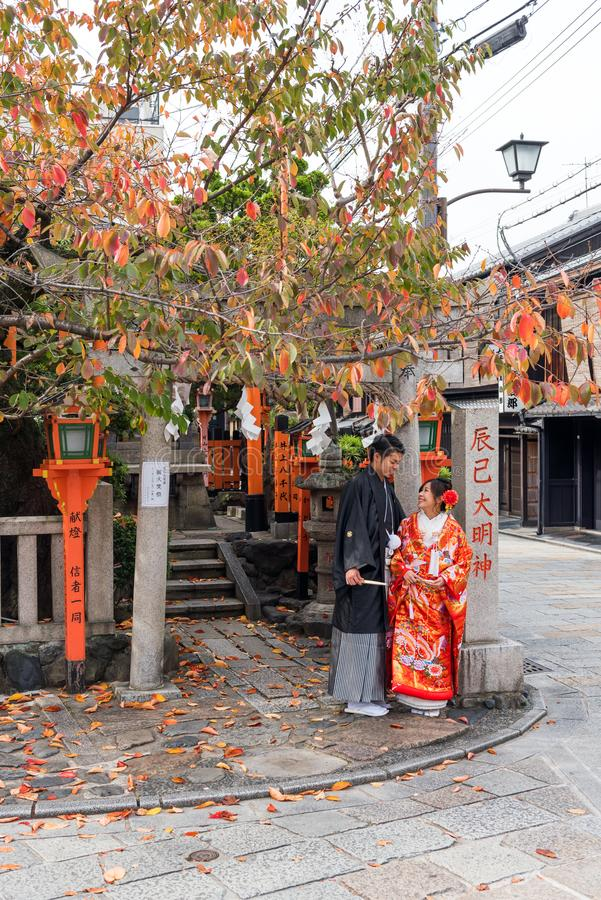 KYOTO, JAPAN - NOVEMBER 7, 2017: A couple in a kimono on a city street. Copy space for text. Vertical. KYOTO, JAPAN - NOVEMBER 7, 2017: A couple in a kimono on stock photos