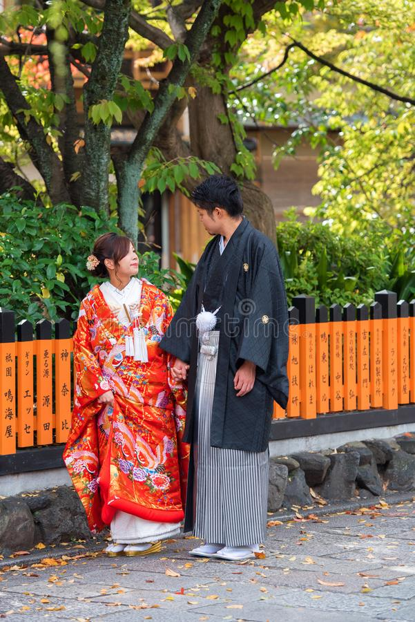 KYOTO, JAPAN - NOVEMBER 7, 2017: Couple in a kimono on a city st. Reet. Vertical. Copy space for text royalty free stock image