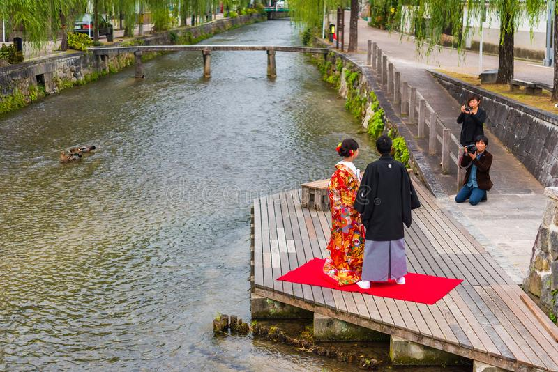 KYOTO, JAPAN - NOVEMBER 7, 2017: Couple in a kimono on the river bank. Copy space for text. KYOTO, JAPAN - NOVEMBER 7, 2017: Couple in a kimono on the river royalty free stock image