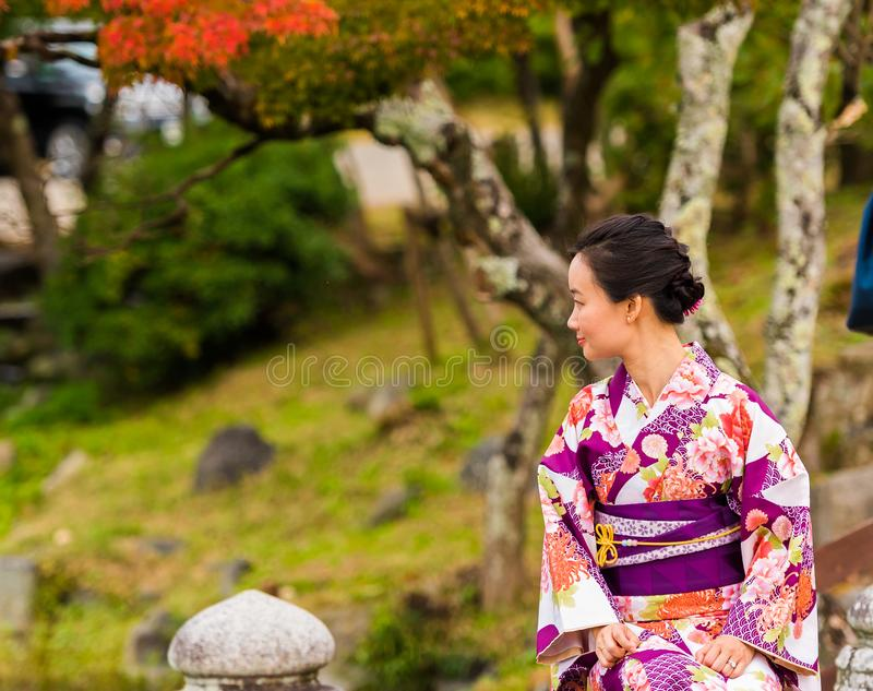 KYOTO, JAPAN - NOVEMBER 7, 2017: A girl in a kimono against the background of a city park. Copy space for text. KYOTO, JAPAN - NOVEMBER 7, 2017: A girl in a stock image
