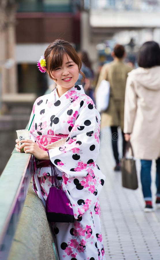 KYOTO, JAPAN - NOVEMBER 7, 2017: A girl in a kimono on a city st. Reet. Vertical royalty free stock images