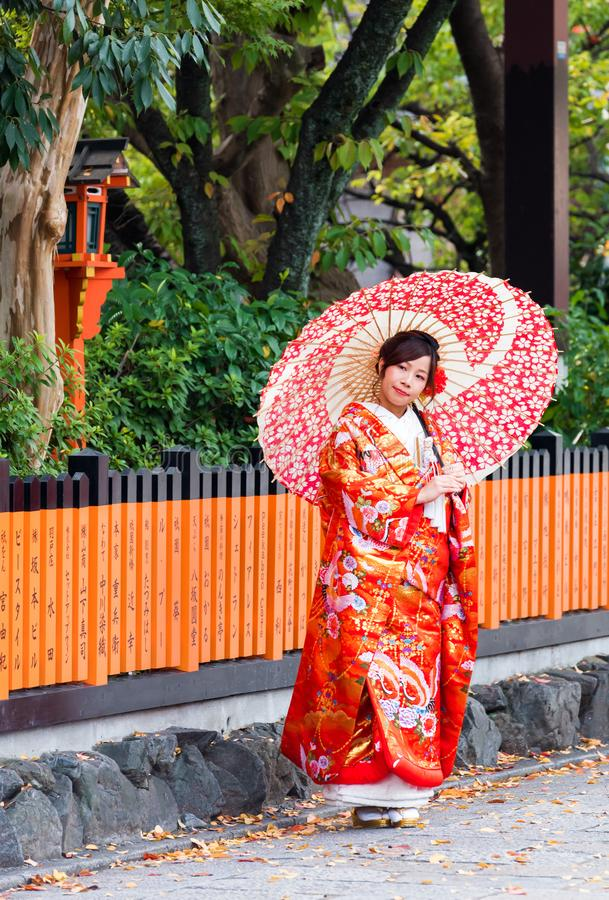 KYOTO, JAPAN - NOVEMBER 7, 2017: A girl in a kimono with an umbrella on a city street. Vertical. Copy space for text. KYOTO, JAPAN - NOVEMBER 7, 2017: A girl in stock photo