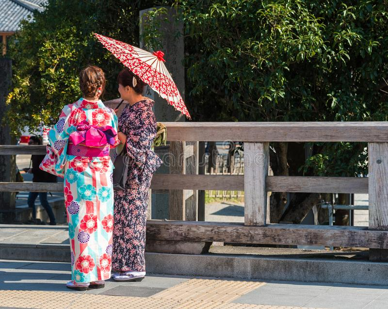 KYOTO, JAPAN - NOVEMBER 7, 2017: Girls in a kimono with an umbrella on a city street. Copy space for text. Back view. KYOTO, JAPAN - NOVEMBER 7, 2017: Girls in stock photos