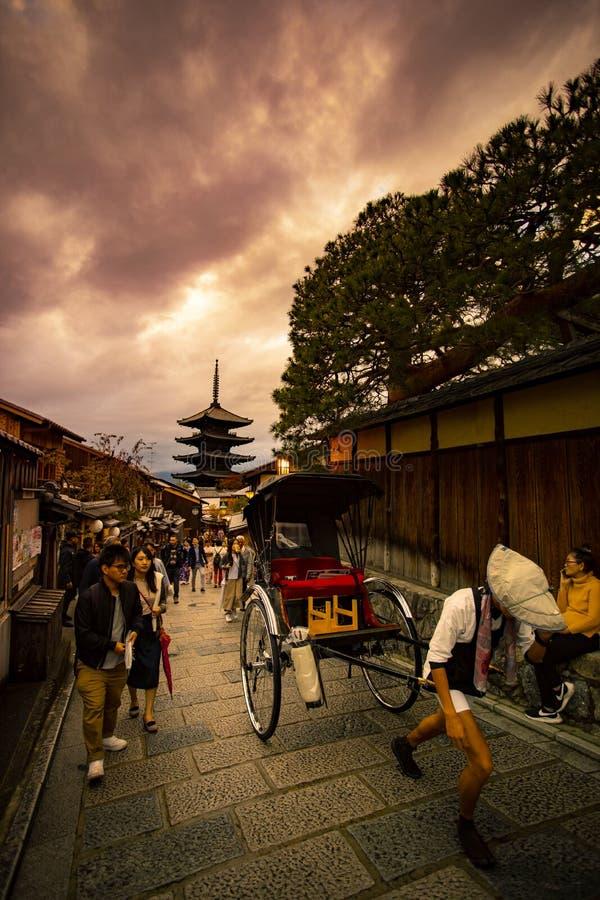 Kyoto Japan - november9,2018: japansk man som drar rickshawen på yasakagatan, yasakarelikskrin en av mest populär resande royaltyfria foton