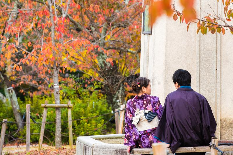 KYOTO, JAPAN - NOVEMBER 7, 2017: A loving couple in a kimono sits on a bench. Copy space for text. KYOTO, JAPAN - NOVEMBER 7, 2017: A loving couple in a kimono royalty free stock photo