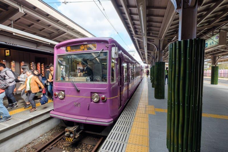 Kyoto Japan - November 11 2017: Traditionella identitetsdrevlilor som parkeras på plattformen med passagerare på arashiyamaen arkivfoton