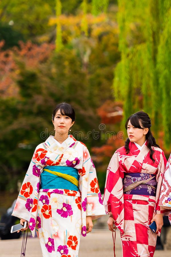 KYOTO, JAPAN - NOVEMBER 7, 2017: Two girls in a kimono on a city street. Copy space for text. Vertical. KYOTO, JAPAN - NOVEMBER 7, 2017: Two girls in a kimono royalty free stock image