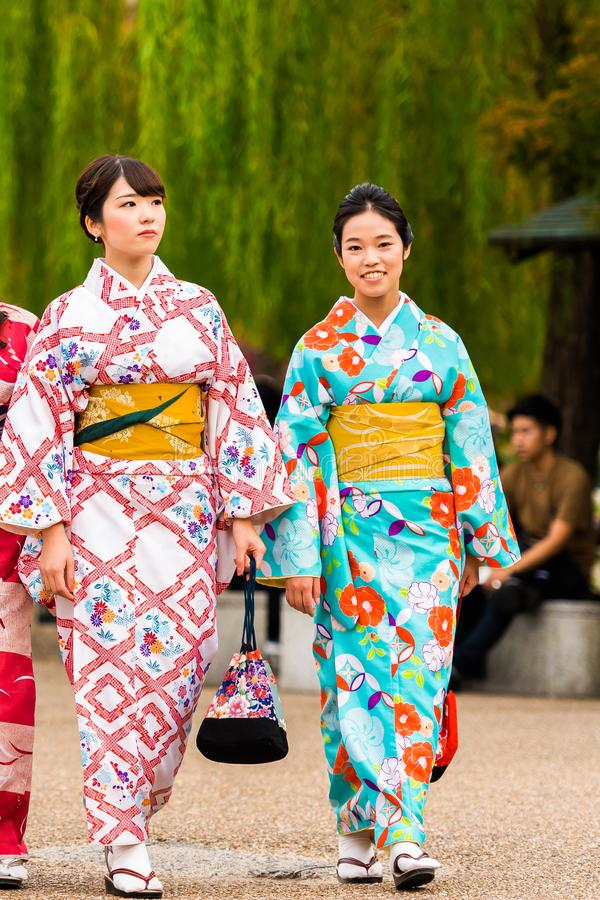 KYOTO, JAPAN - NOVEMBER 7, 2017: Two girls in a kimono on a city street. Copy space for text. Vertical. KYOTO, JAPAN - NOVEMBER 7, 2017: Two girls in a kimono royalty free stock photo