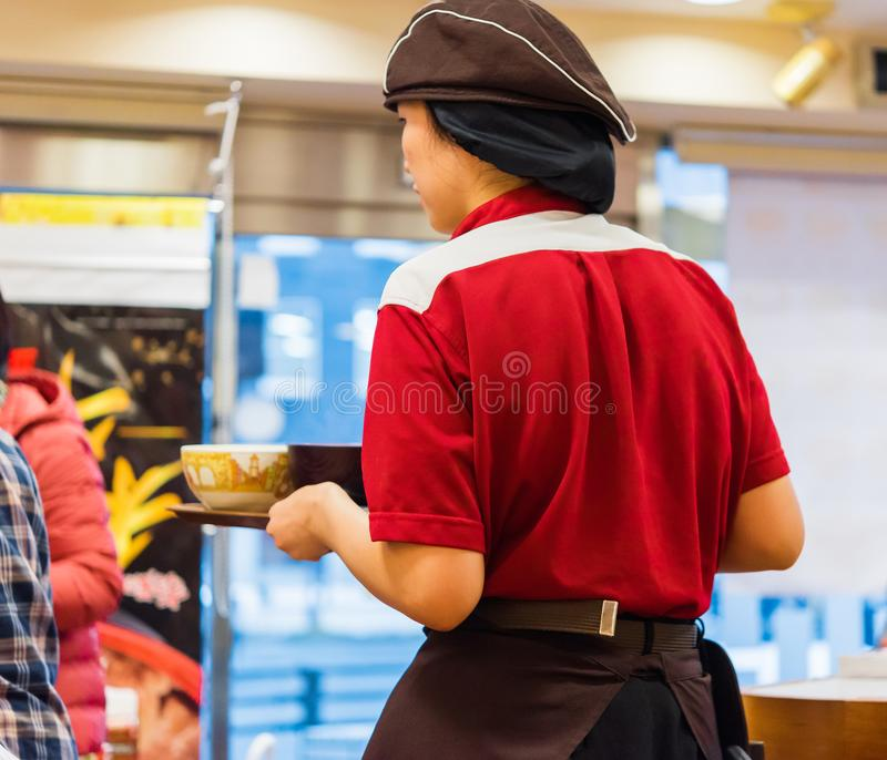 KYOTO, JAPAN - NOVEMBER 7, 2017: A waitress in a cafe. Close-up. Back view. royalty free stock photos