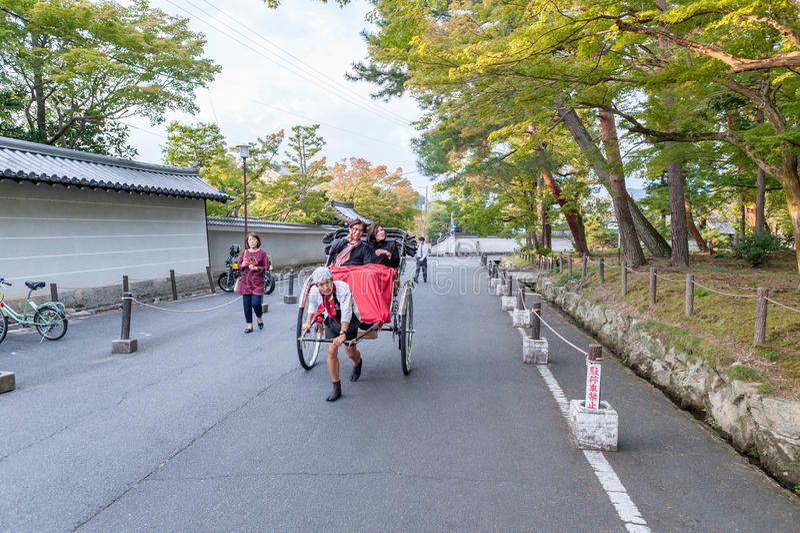 KYOTO JAPAN - OKTOBER 08, 2015: Rickshaw i Tokyo, Japan Med lokalen Poople och Shite parkera i bakgrund arkivfoto