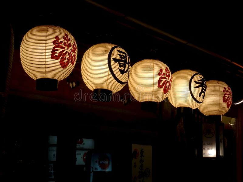 Six traditional Japanese paper lanterns hanging outside a restaurant in Kyoto stock images