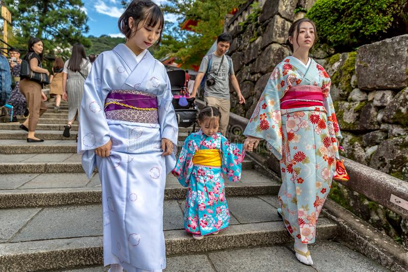 Kyoto Japan - två kvinnor och lite barndressing som geishas som går i en tempel i Kyoto, Japan arkivbilder