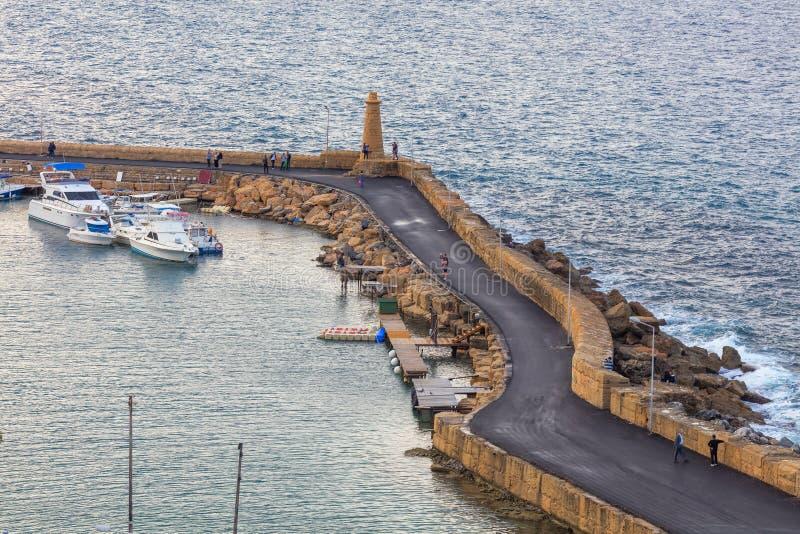 KYRENIA, СЕВЕРНЫЙ КИПР - 29-ОЕ НОЯБРЯ 2015: люди идя пристанью на Средиземном море плавают вдоль побережья на вечере стоковое фото rf