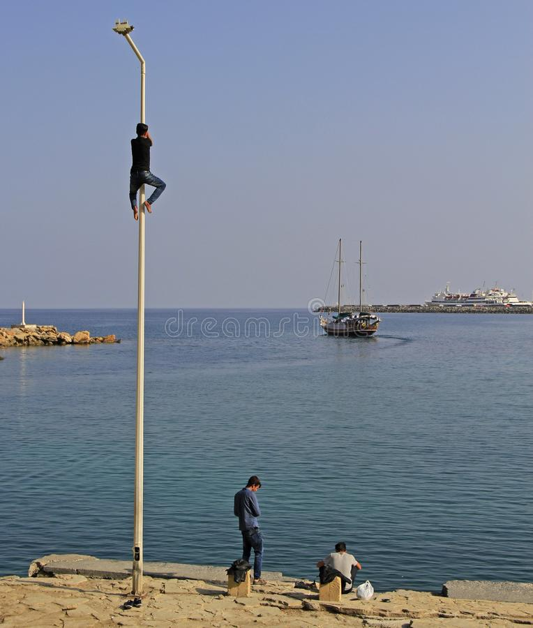 Adolescent are climbing pole outdoor in Kyrenia, Cyprus royalty free stock photography