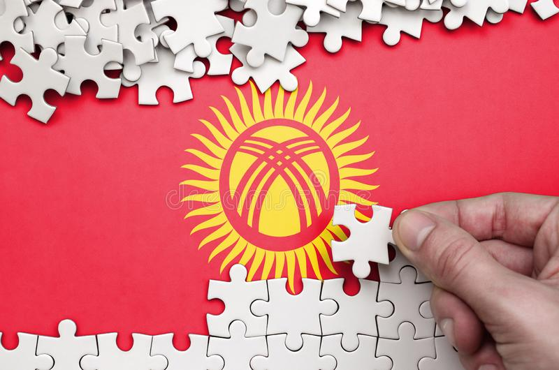 Kyrgyzstan flag is depicted on a table on which the human hand folds a puzzle of white color royalty free stock images