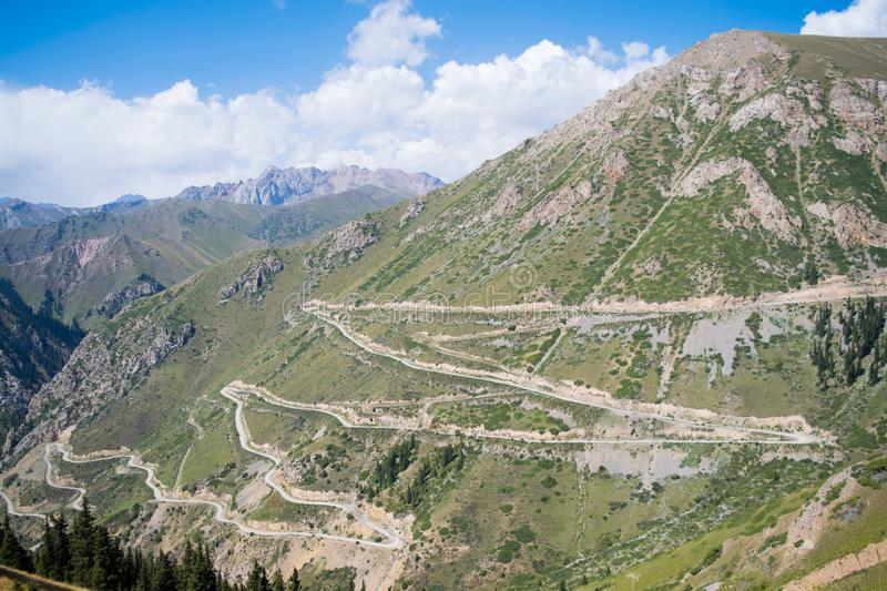 Kyrgyzstan road in the mountains. Zigzag road in the Kyrgyzstan mountains going to the valley from the top stock images