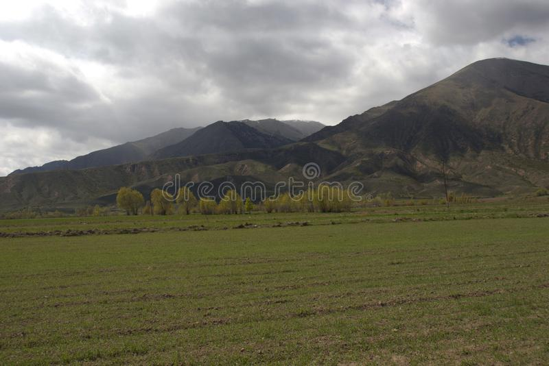 Kyrgyzstan& x27;s mountain view from Grigorievka village near Issyk-Kul lake in May royalty free stock photos
