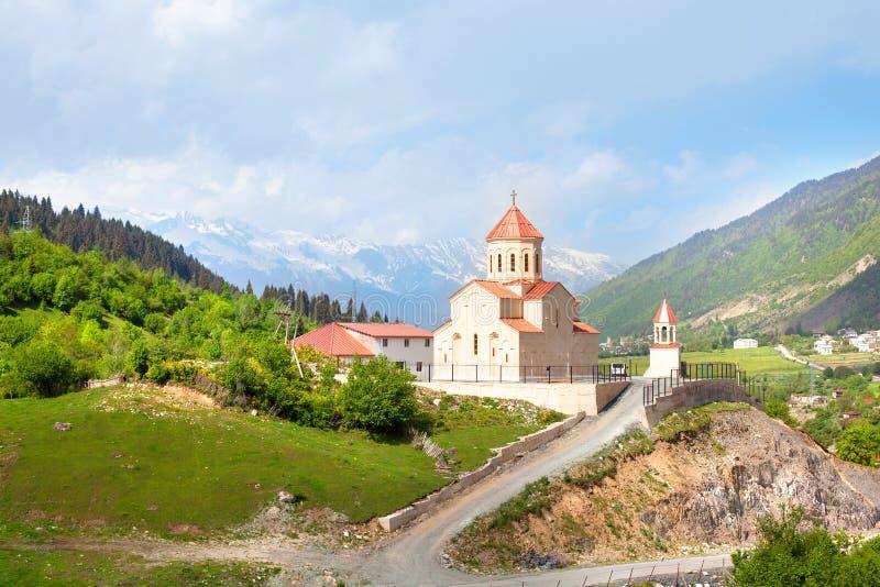 Kyrka av St Nicholas på kullen av bergbakgrund i Mestia, Georgia royaltyfri foto