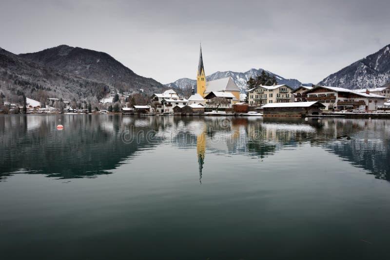 Kyrka bredvid en sjö i snön arkivfoton