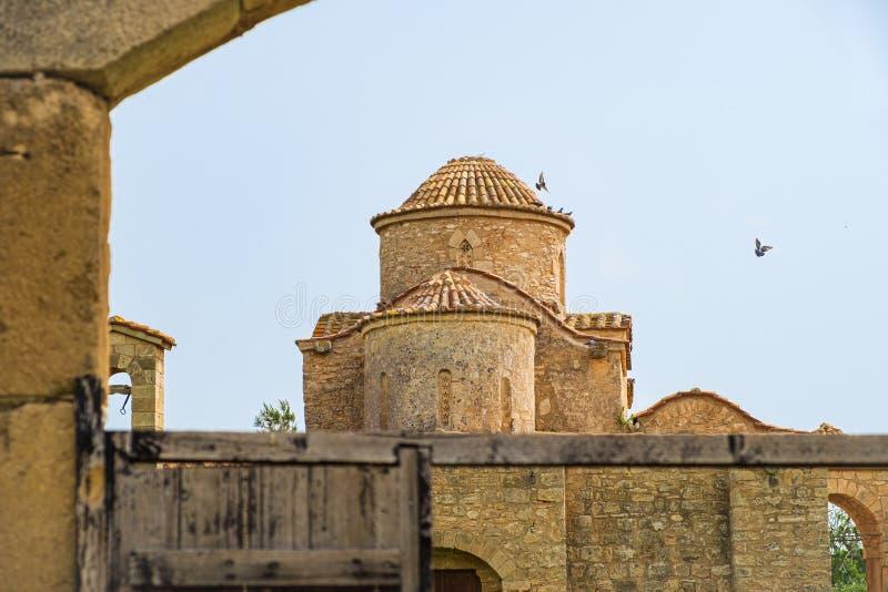 Kyrka för kloster Panayia Kanakaria för 6th århundrade bysantinsk i Lythrangomi, Cypern med duvor som flyger av dess kupol arkivfoto