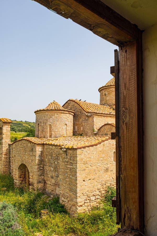 Kyrka för kloster Panayia Kanakaria för 6th århundrade bysantinsk i Lythrangomi, Cypern viewd till och med ett klosterfönster arkivfoto