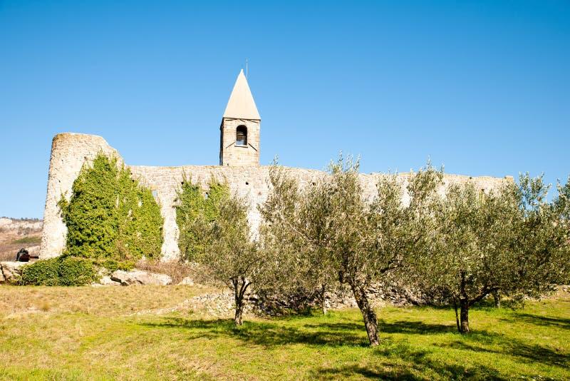 Kyrka f?r helig trinity och medeltida f?stning i olivgr?nt sp?r i Hrastovlje Slovenien Centraleuropa arkivfoto