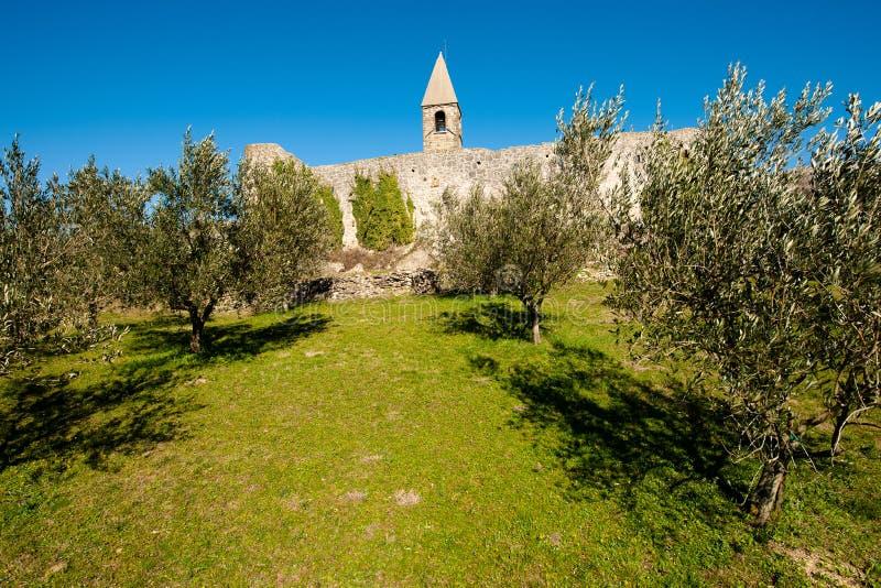 Kyrka f?r helig trinity och medeltida f?stning i olivgr?nt sp?r i Hrastovlje Slovenien Centraleuropa arkivbild