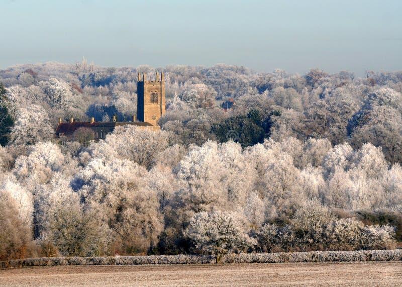 Kyrka i de iskalla vita vinterträden Fristad eller säkerhet arkivfoto