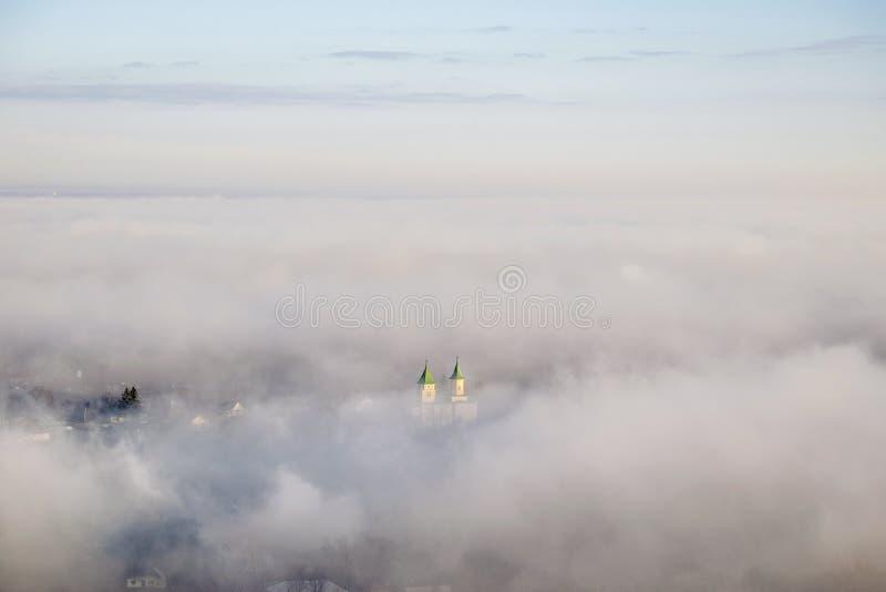 Kyrka i dimma från över royaltyfria foton