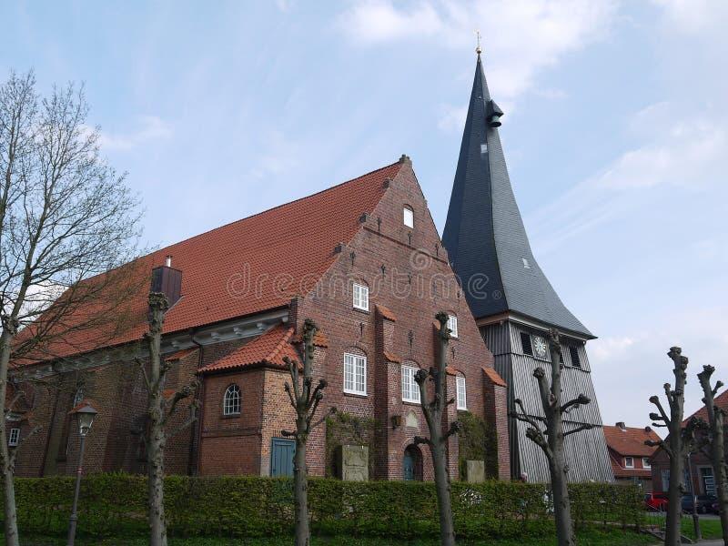 Kyrka med att slutta väggar i den Alte landTyskland, skepp som göras av tegelsten, kyrkligt torn panelled med trä royaltyfri foto