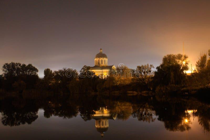 Kyrka nära sjön på nattljus royaltyfri bild