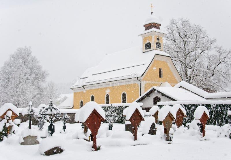 Kyrka och gravar i vintern som täckas med snö royaltyfria bilder