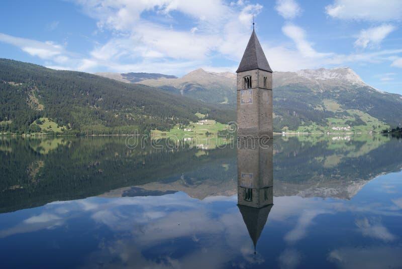 Kyrkaklockatorn som doppas i den italienska sjön med reflexion arkivfoton