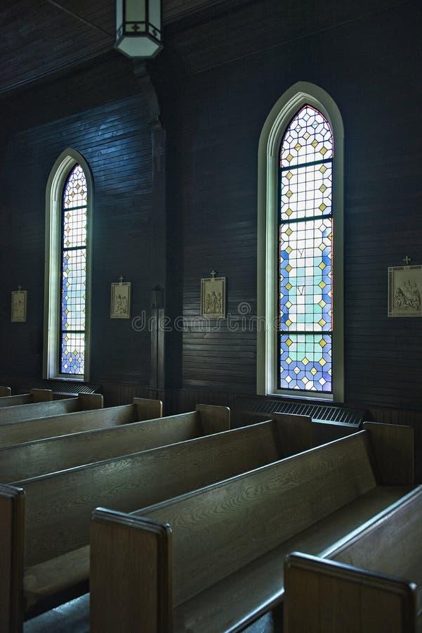 Kyrkakyrkbänkar med målat glass Windows royaltyfri bild