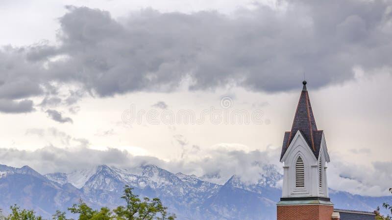 Kyrkakyrktorn mot berget och molnig himmel royaltyfria bilder