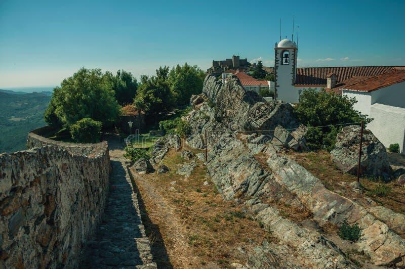 Kyrkakyrktorn och hus med den kalkade väggen över vaggar i Marvao royaltyfria foton