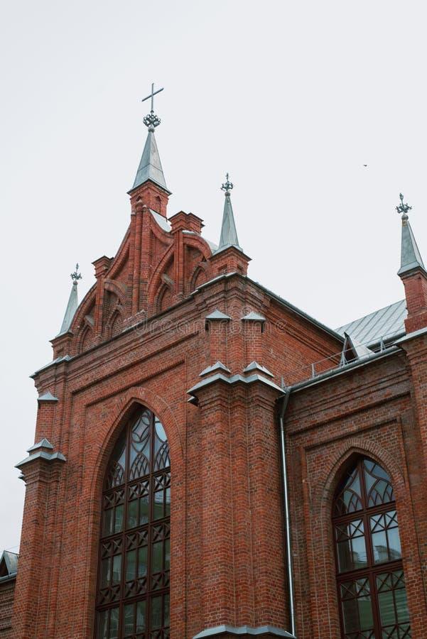 Kyrkan är av röd tegelsten, med kors och tunna fönster royaltyfri fotografi