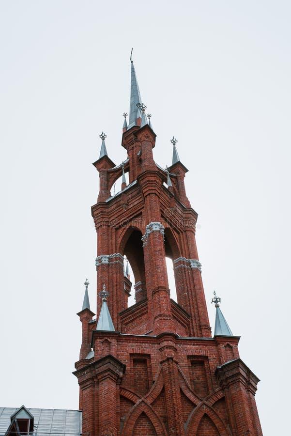 Kyrkan ?r av r?d tegelsten, med kors och tunna f?nster royaltyfri bild