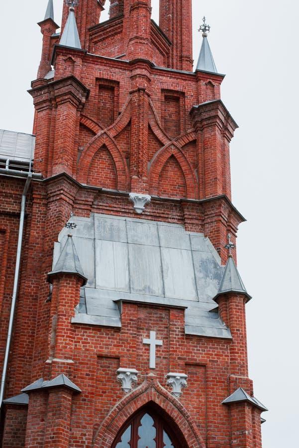 Kyrkan ?r av r?d tegelsten, med kors och tunna f?nster arkivbilder